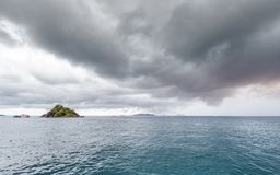 Den härliga sceniska ön med att resa fartyget, medan regna strom nära, kommer royaltyfria foton