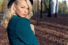Den härliga sexiga älsklingen en lycklig flicka blondinen i ett varm omslag och hatt går i staden parkerar i solig höstdag Arkivfoton