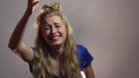 Den härliga sexiga blonda flickan i blåttklänning är Laughting av det din oerhörda skämtet i studio med ljus bakgrund lager videofilmer