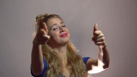 Den härliga sexiga blonda flickan i blåttklänning visar tummar upp till dig som betyder dig beträffande ` det bästa i studio med  lager videofilmer