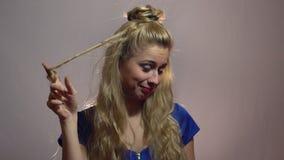 Den härliga sexiga blonda flickan i blåttklänning visar tummar upp till dig som betyder dig beträffande ` det bästa i studio med  arkivfilmer
