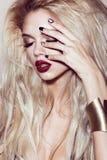 Den härliga sexiga blonda flickan med sinnliga kanter, modehår, svart konst spikar Härlig le flicka Royaltyfri Fotografi
