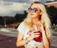 Den härliga sexiga blonda flickan rymmer en hand per exponeringsglas av den nya kalla sommardrinken sommarsemester i värmen, fris Royaltyfria Bilder