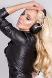 Den härliga sexiga blonda kvinnan med långt hår och gör perfekt kroppen i svart läderomslag med hörlurar Royaltyfria Foton