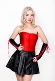 Den härliga sexiga blonda kvinnan med stora bröst i en röd korsett- och kortslutningssvart kringgår Arkivfoton
