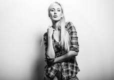 Den härliga sexiga blonda kvinnan poserar mot studiobakgrund Svart-vit foto Arkivfoton