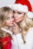Den härliga sexiga blonda kvinnliga den modellmodern och dottern klädde som Santa Claus i ett rött lock Fotografering för Bildbyråer