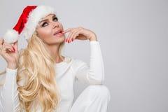 Den härliga sexiga blonda kvinnliga modellen klädde som Santa Claus i ett rött lock Arkivbild