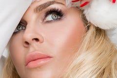 Den härliga sexiga blonda kvinnliga modellen klädde som Santa Claus i ett rött lock Royaltyfria Bilder
