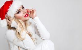 Den härliga sexiga blonda kvinnliga modellen klädde som Santa Claus i ett rött lock Arkivfoton
