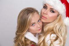 Den härliga sexiga blonda kvinnliga den modellmodern och dottern klädde som Santa Claus i ett rött lock med på viten Arkivbild