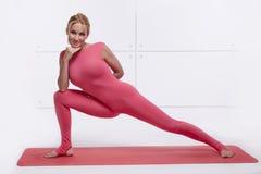 Den härliga sexiga blondinen med det perfekta idrotts- slanka diagramet som är förlovat i yoga, pilates, övningskondition, leder  Arkivbild