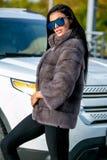 Den härliga sexiga brunetten i solglasögon och ett pälslag går ner gatan på solig dag och ser bort Sen höst eller tidig winte fotografering för bildbyråer