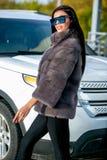 Den härliga sexiga brunetten i solglasögon och ett pälslag går ner gatan på solig dag och ser bort Sen höst eller tidig winte arkivfoton