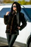 Den härliga sexiga brunetten i solglasögon och ett pälslag går ner gatan på solig dag och ser bort Sen höst eller tidig winte arkivfoto