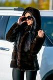 Den härliga sexiga brunetten i solglasögon och ett pälslag går ner gatan på solig dag och ser bort Sen höst eller tidig winte royaltyfria bilder