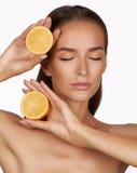 Den härliga sexiga brunettkvinnan med citruns på en vit bakgrund, sund mat, smaklig mat som är organisk bantar, ler sunt Royaltyfria Foton