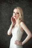 Den härliga sexiga damen i bärande bröllop för elegant vit damunderkläder skyler Stående av flickan för modemodell inomhus Blond  Arkivfoton