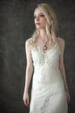 Den härliga sexiga damen i bärande bröllop för elegant vit damunderkläder skyler Stående av flickan för modemodell inomhus Blond  Arkivbilder