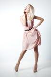 Den härliga sexiga eleganta slående blonda kvinnan med ljus makeup i rosa färger klär med spensliga ben för dlinnymien i studio p Arkivfoto