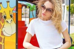 Den härliga sexiga flickan i en vit T-tröja och kortslutningar i dzhisovyhnöjesfältet i solglasögon, hår framkallar vind Royaltyfri Foto