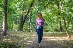 Den härliga sexiga flickan i jeans och omslaget som går bland träden i höst, parkerar och poserar känslomässigt nära en lykta Fotografering för Bildbyråer