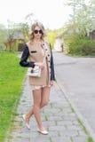 Den härliga sexiga flickan med fulla kanter går i solglasögon i ett lag med en handväska till och med stadsgatorna Royaltyfri Bild