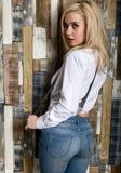 Den härliga sexiga flickan med stora klantskallar i jeans för en tappning och den vita skjortan poserar nära en trävägg Royaltyfria Foton