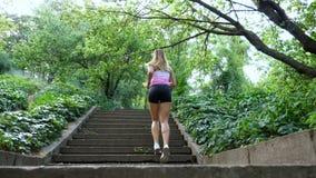 Den härliga sexiga idrotts- unga blonda kvinnan i en T-tröja och kortslutningar, körningar uppför trappan, i skogen, parkerar, i  arkivfilmer