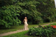 Den härliga sexiga kvinnan går i parkera fotografering för bildbyråer