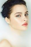 Den härliga sexiga kvinnan i bad med mjölkar den kosmetiska kroppen för brunnsorten royaltyfri bild