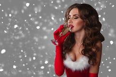 Den härliga sexiga kvinnan i Santa Claus beklär att dricka champagne över en grå bakgrund med snö Royaltyfria Bilder
