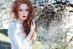 Den härliga sexiga rödhåriga flickan med fräknar med röd läppstift på hennes kanter near blommande träd i staden på en solig klar Arkivbild