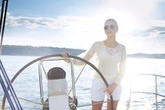 Den härliga sexiga unga blonda kvinnan som rider ett fartyg på vattnet, resplanen, härlig makeup, kläder, sommar, sol, gör perfek Royaltyfri Foto