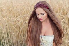 Den härliga sexualintelliganceflickamodellen i blåttklänning med rosa kantdesign visar en kant på huvudet i ett fält på ett solig Royaltyfri Fotografi