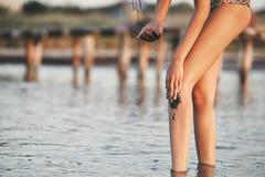 Den härliga sexuella flickan i havet på solnedgången målar sig med medicinsk gyttja Royaltyfri Bild