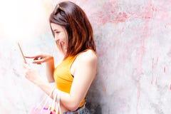 Den härliga shoppingkvinnan använder smartphonen och internet direktanslutet arkivbilder