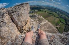 Den härliga sikten av en man från en klippa av vaggar, det mäktiga landskapet, första-personen sikten, fisheyedistorsion arkivfoto