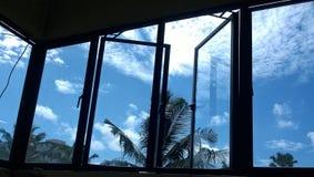 Den härliga sikten av himmel oppen igenom fönster Arkivbilder
