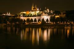 Den härliga sikten av den Prague slotten på natten reflekterade på den Vltava floden Royaltyfria Bilder