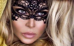 Den härliga sinnliga blonda kvinnan med karnevalmaskeringen på hennes framsida står på en svart bakgrund Royaltyfri Bild