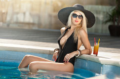 Den härliga sinnliga blondinen med solglasögon och svart förlägga i barack att koppla av i pölen med en fruktsaft Attraktiv lång  Royaltyfri Foto
