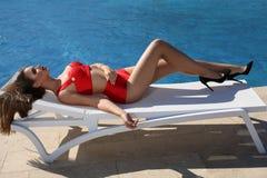 Den härliga sinnliga flickan med blont hår bär den lyxiga röda baddräkten Fotografering för Bildbyråer