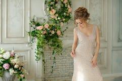Den härliga sinnliga flickan som är blond i beige klänning ler försiktigt, i Royaltyfria Foton