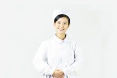 Den härliga sjuksköterskan på en vit isolerade bakgrund, smi Arkivbilder