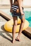 Den härliga slanka flickan i sexig randig bikini tar av hennes kortslutningar Royaltyfri Foto