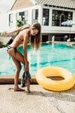 Den härliga slanka flickan i sexig randig bikini tar av hennes kortslutningar Royaltyfri Bild