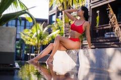 Den härliga slanka sexiga kvinnan som bär den röda bikinin, kopplar av nära utomhus- vattenpöl på semesterort Arkivfoto