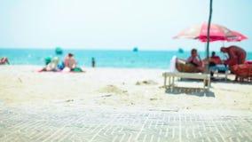 Den härliga soliga avskilda stranden på ferierna som ser över halva, begravde drivved i sanden med mjukt fokusfolk och lager videofilmer
