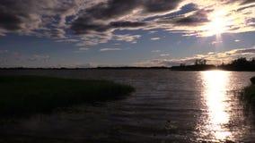Den härliga solnedgången över sjö- och solreflexioner på flyttning vinkar lager videofilmer